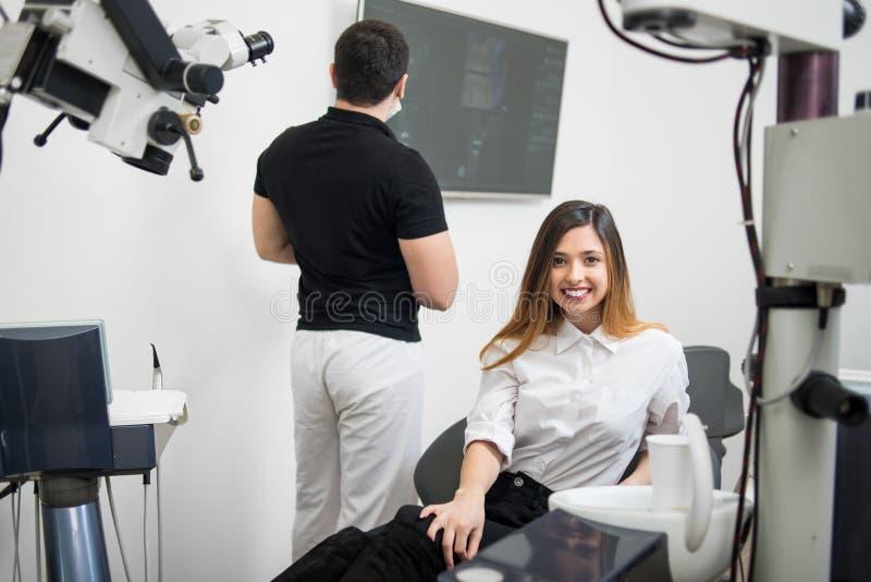 Mooie vrouwelijke geduldige zitting als tandvoorzitter, die na behandeling bij moderne tandkliniek glimlachen stock foto's