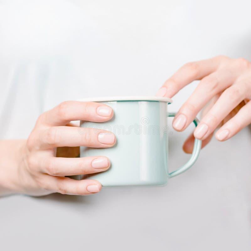 Mooie vrouwelijke handen die een emailkop houden Manicure met naakt nagellak De ruimte van het exemplaar royalty-vrije stock afbeelding