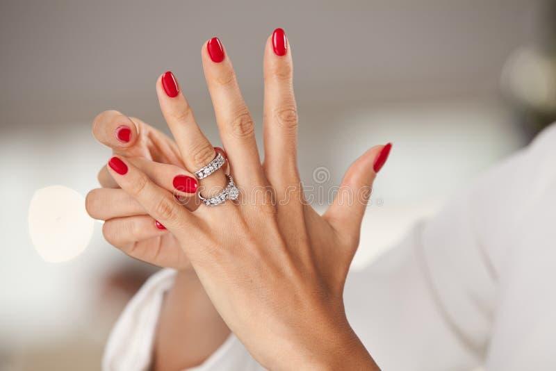Mooie vrouwelijke handen met rode spijkers en elegante diamantringen stock fotografie