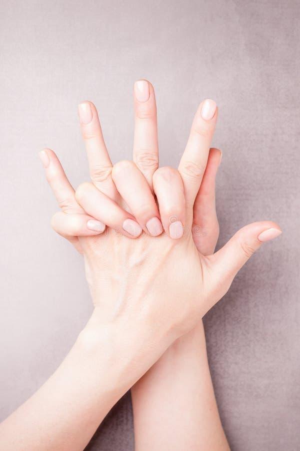Mooie vrouwelijke handen op een grijze achtergrond Manicure met naakt nagellak Het concept van de manicurezorg De ruimte van het  stock fotografie