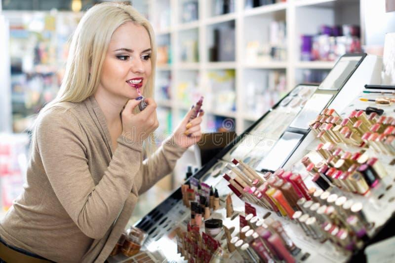 Mooie vrouwelijke klant die rode lippenstift in make-upsectie kopen stock afbeeldingen