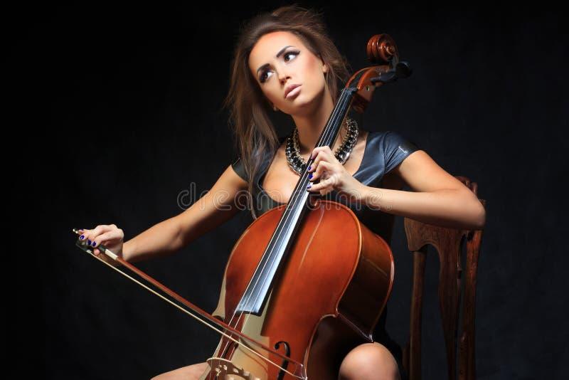 Mooie vrouwelijke musicus die een cello spelen stock foto's