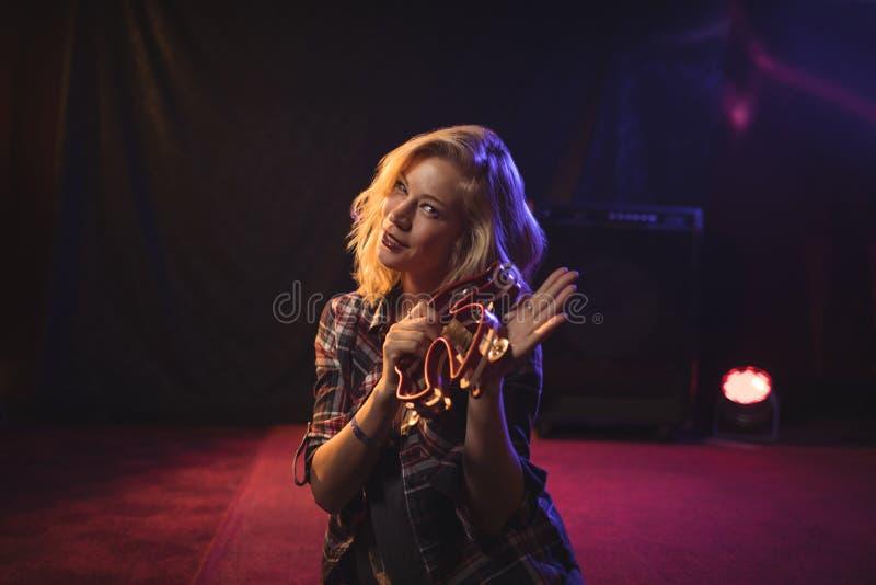 Mooie vrouwelijke musicus het spelen tamboerijn in nachtclub stock afbeeldingen