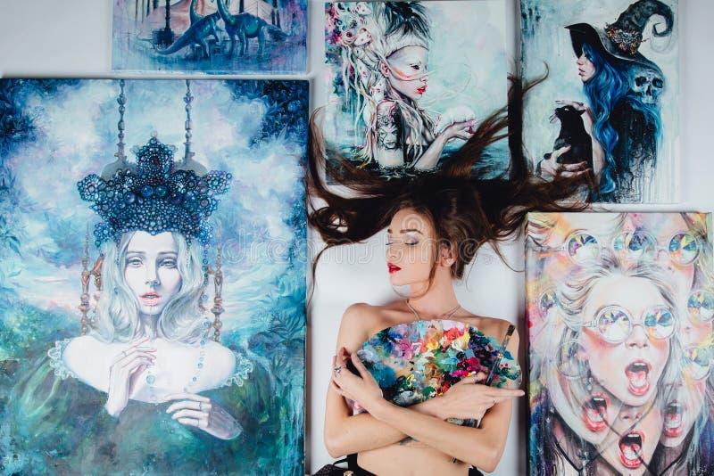 Mooie vrouwelijke Naakte die kunstenaar door schilderijencanvas wordt omringd op de vloer witte achtergrond Borstels en palet royalty-vrije stock foto's