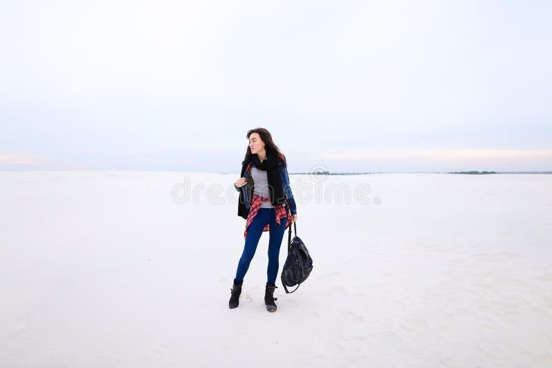 Mooie vrouwelijke persoon die op sneeuwachtergrond lopen en jeans met zak dragen royalty-vrije stock afbeeldingen