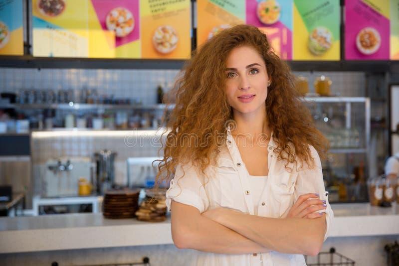 Mooie vrouwelijke rode haired barista die camera en het glimlachen bekijken royalty-vrije stock fotografie