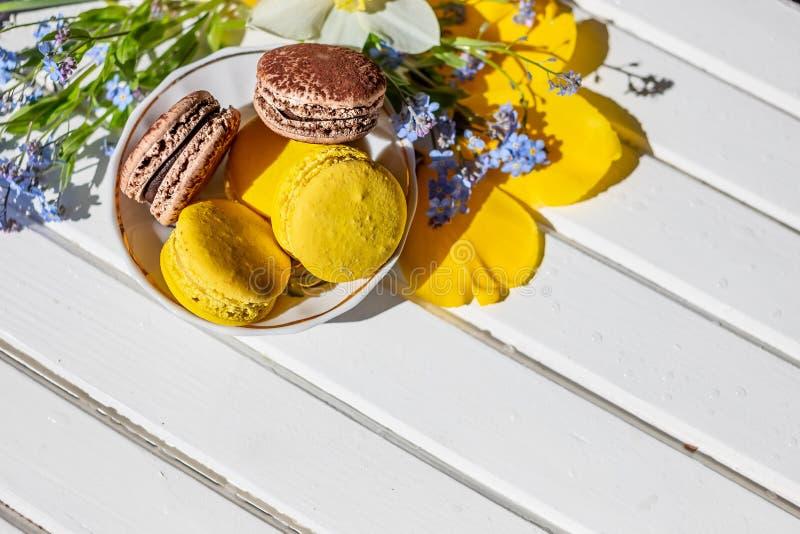 Mooie vrouwelijke samenstelling, heldere kleuren Franse makaronsnoepjes en tedere bloemenbloesems op witte houten royalty-vrije stock afbeelding