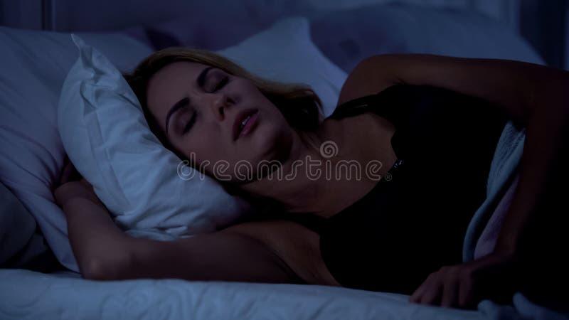 Mooie vrouwelijke slaap op bed bij nacht, die na harde werkdag, gesnurk rusten stock foto's