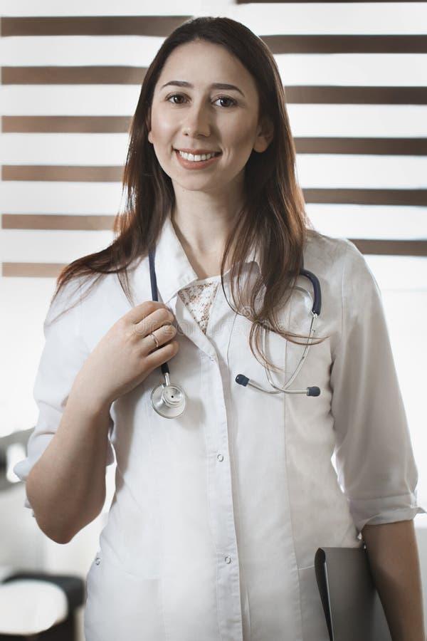 Mooie vrouwelijke slimme geneeskunde arts in camera en KMIO die kijken stock afbeeldingen