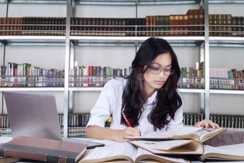 Mooie vrouwelijke student die in een bibliotheek bestuderen stock foto