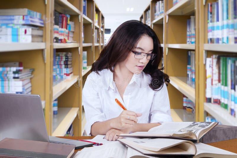 Mooie vrouwelijke student die schoolwork in bibliotheek doen stock foto