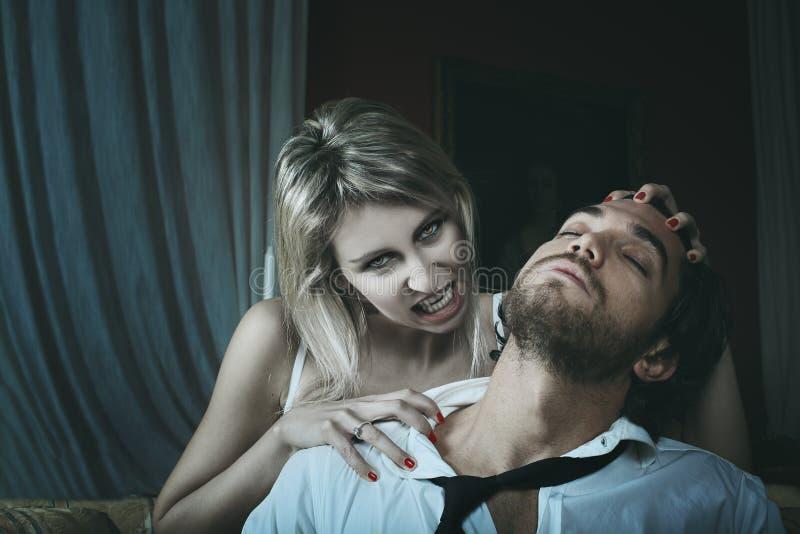 Mooie vrouwelijke vampier en haar prooi stock afbeeldingen