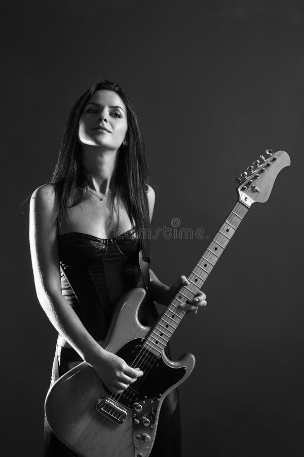 Mooie vrouwelijke zwart-witte gitaarspeler stock fotografie