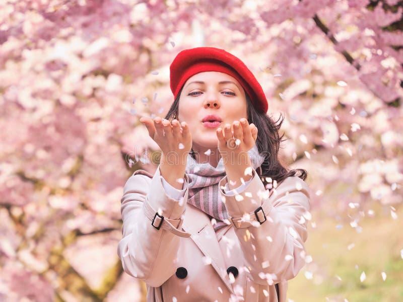 Mooie Vrouwen blazende bloemblaadjes in haar handen royalty-vrije stock foto