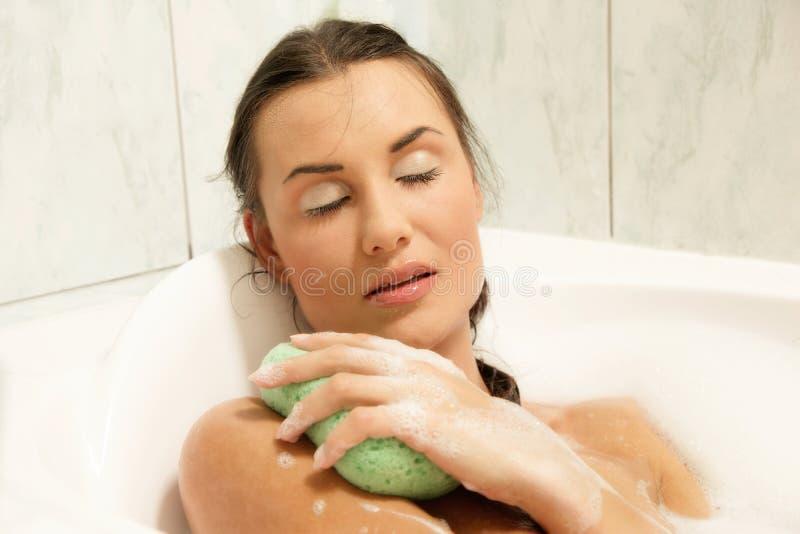 Mooie vrouwen die in haar bad ontspannen stock afbeeldingen