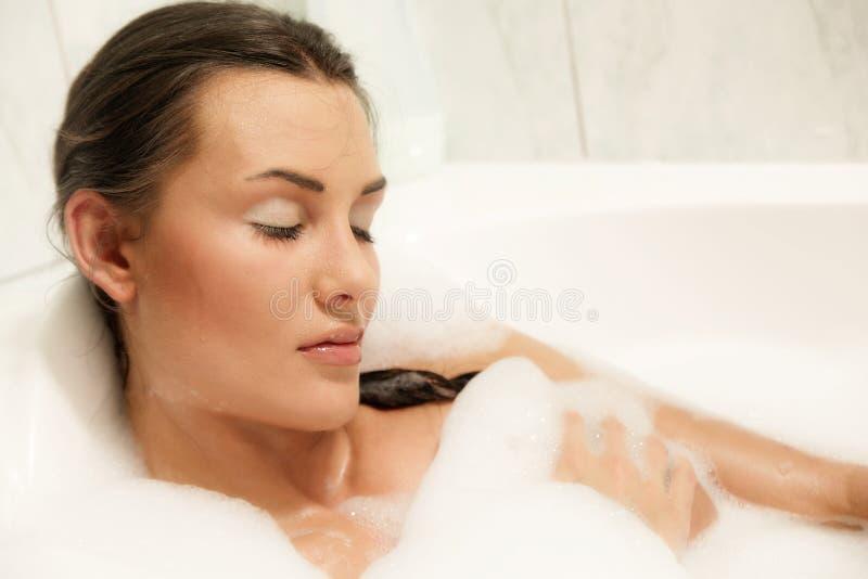 Mooie vrouwen die in haar bad ontspannen stock foto