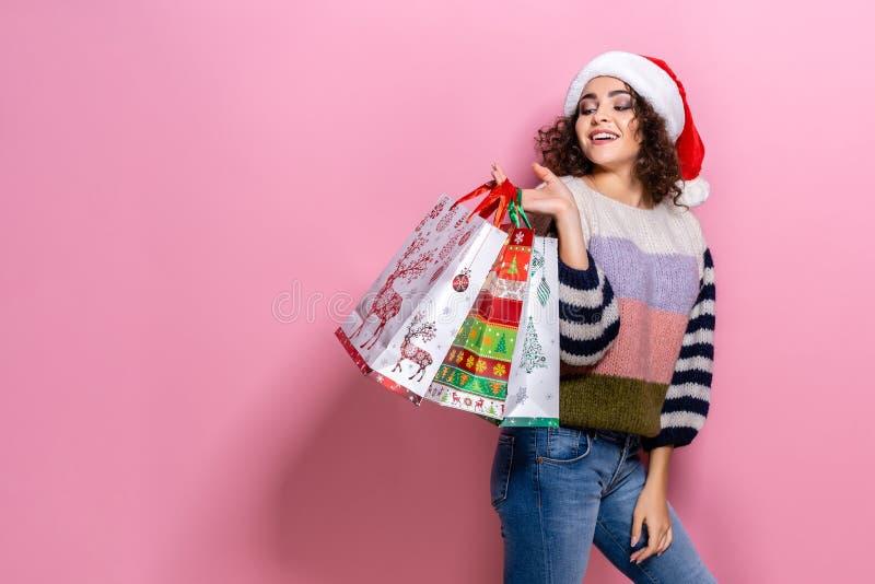 Mooie vrouwen die heldere Kerstmis dragen die kleurrijke het winkelen zakken dragen Op roze achtergrond Kerstmis die winkelen en stock foto