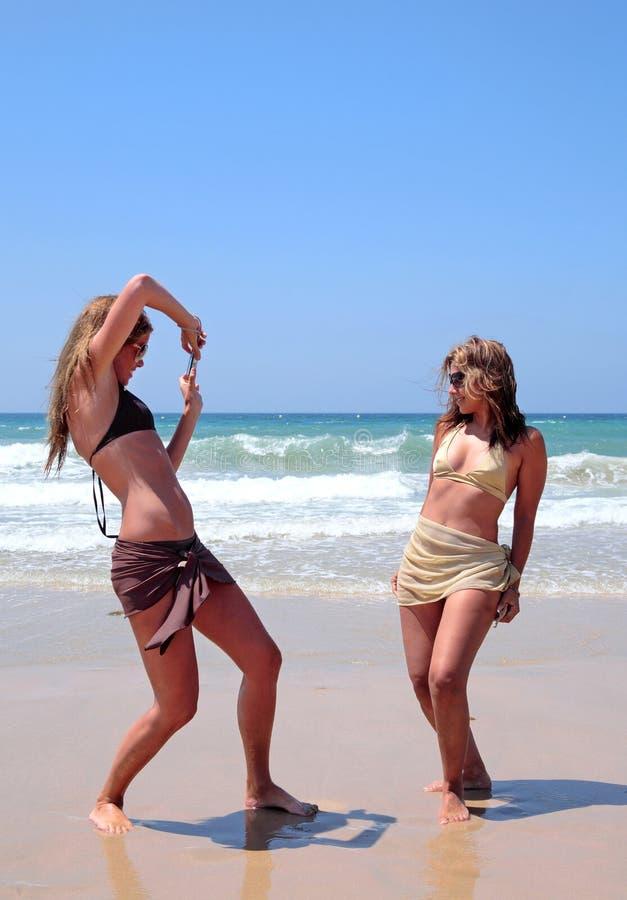 Mooie vrouwen die op strand spelen stock afbeeldingen