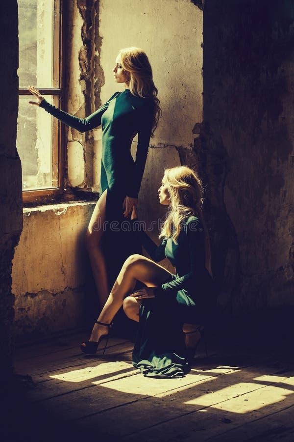 Mooie vrouwen in groene kleding dichtbij venster stock afbeelding
