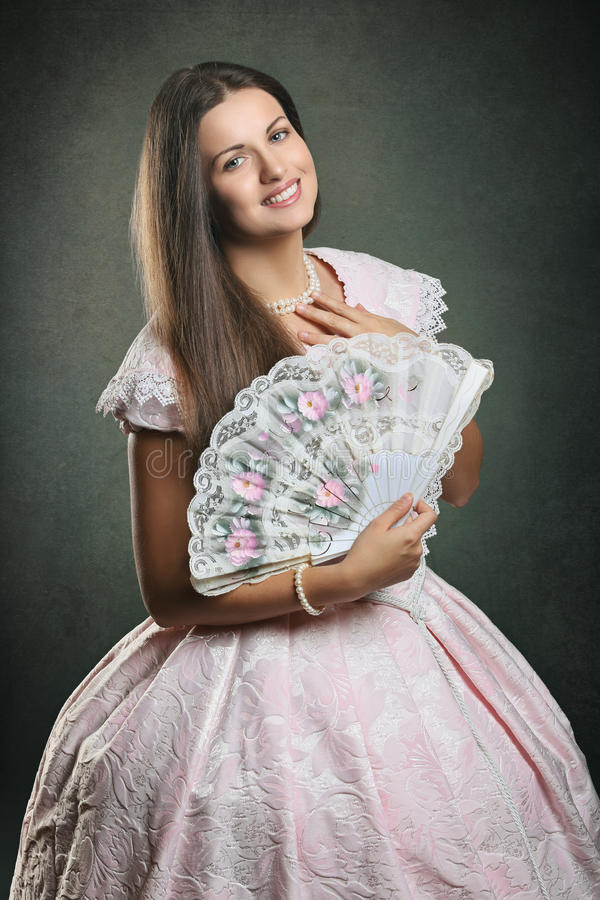 Mooie vrouwen historische kleding met bloemenventilator stock foto