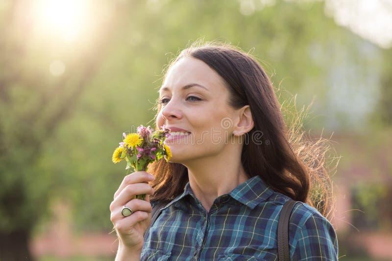 Mooie vrouwen ruikende bloemen royalty-vrije stock afbeelding