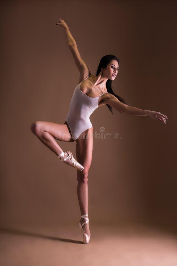 Mooie vrouwenballetdanser die over beige dansen royalty-vrije stock foto
