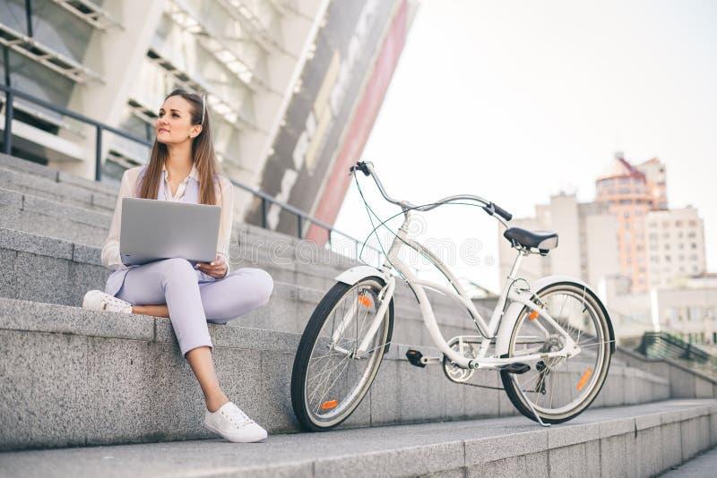 Mooie vrouwenbeambte die bij middagpauze aan laptop werken stock foto