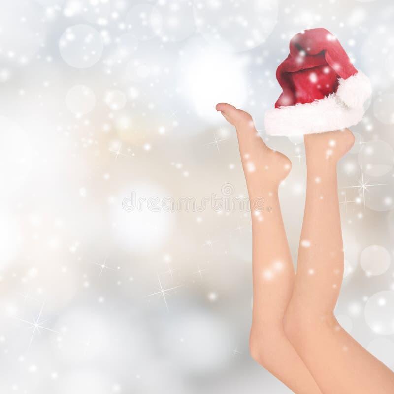 Mooie vrouwenbenen, Kerstmisachtergrond stock fotografie