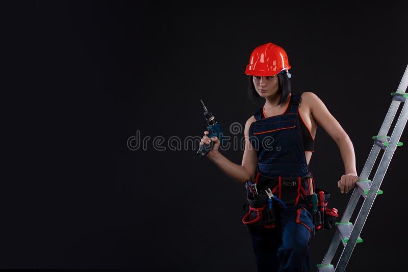 Mooie vrouwenbouwer in helm met boor in haar handen die zich op een ladder bevinden en weg op zwarte achtergrond kijken royalty-vrije stock fotografie
