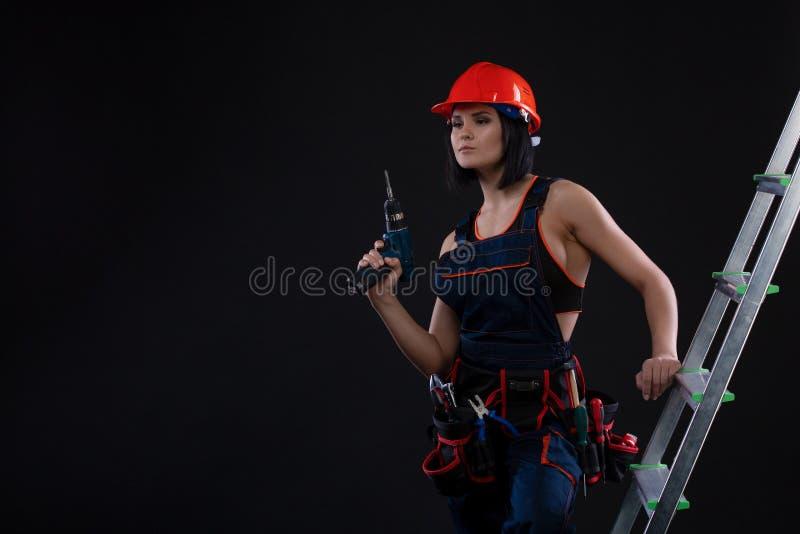 Mooie vrouwenbouwer in helm met boor in haar handen die zich op een ladder bevinden en weg op zwarte achtergrond kijken royalty-vrije stock foto's