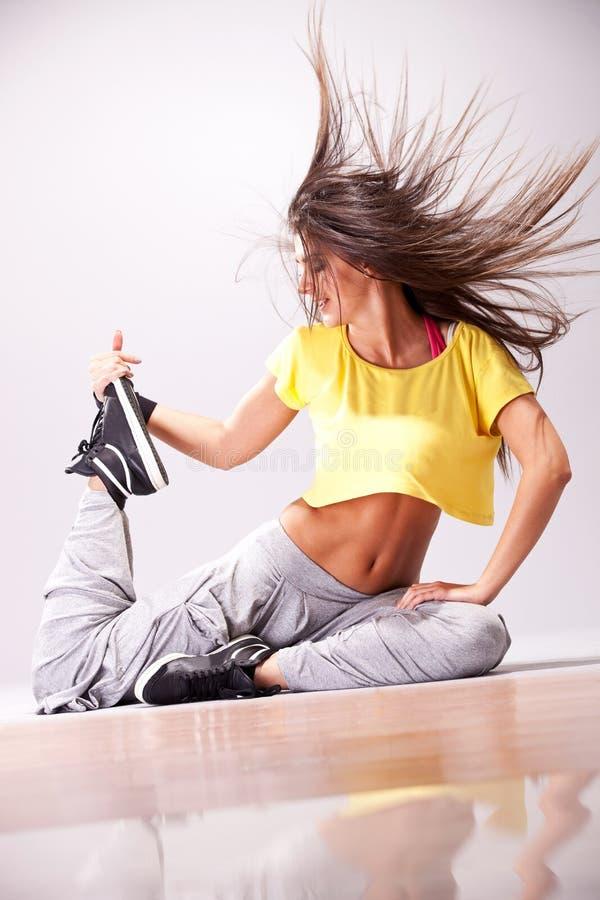 Mooie vrouwendanser die op de vloer rust stock afbeeldingen