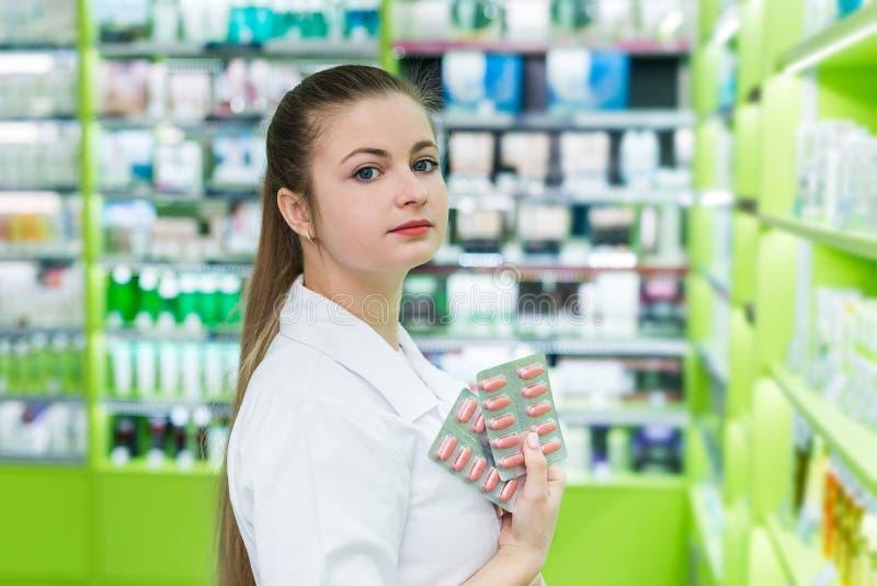 Mooie vrouwendrogist die sommige pillen in blaar tonen royalty-vrije stock foto