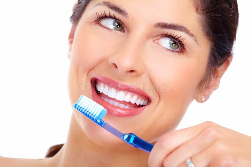 Mooie vrouwenglimlach met een tandenborstel. stock foto