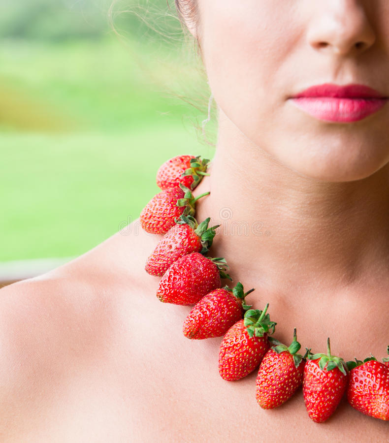 Mooie vrouwenhals met rode die parels van verse aardbei worden gemaakt stock afbeelding