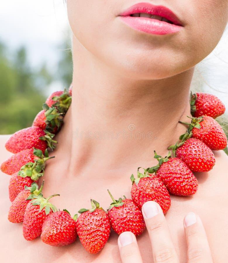 Mooie vrouwenhals met rode die parels van verse aardbei worden gemaakt royalty-vrije stock foto's