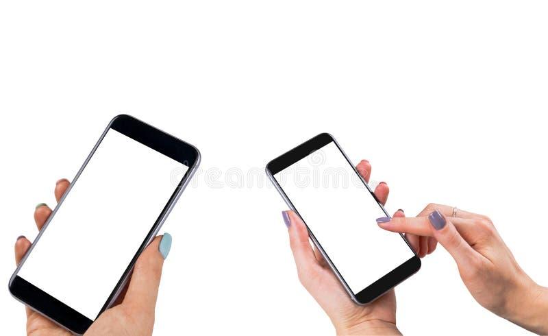 Mooie Vrouwenhanden die slimme telefoon twee met het geïsoleerde witte scherm houden Bedrijfswerkplaats met exemplaarruimte Lege  stock fotografie