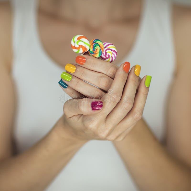 Mooie vrouwenhanden met regenboognagellak die kleurrijke werveling houden lollypops, grappige vrolijk stock fotografie