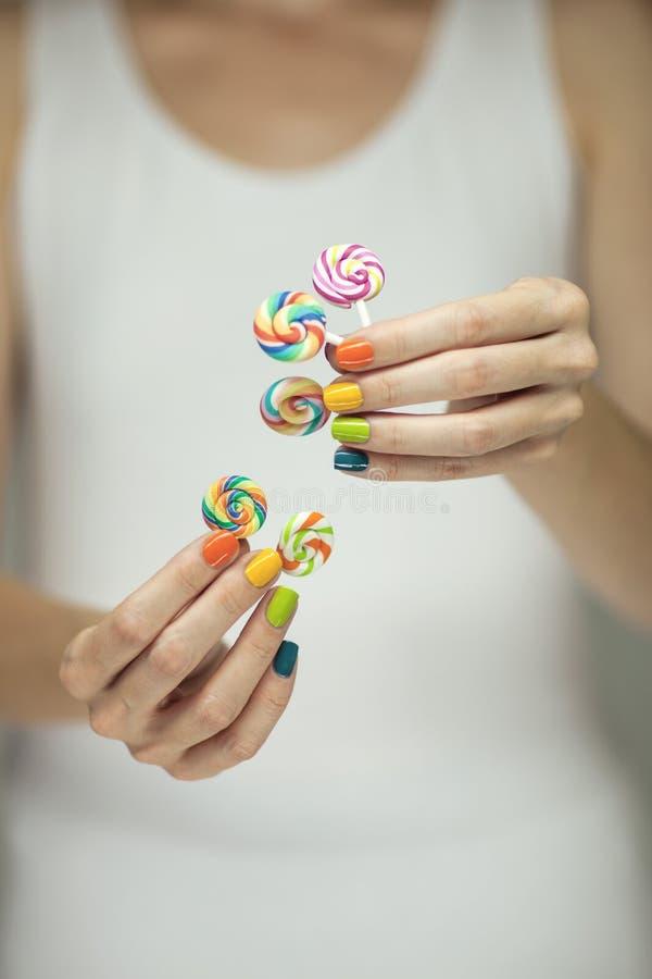 Mooie vrouwenhanden met regenboognagellak die kleurrijke werveling houden lollypops, grappige vrolijk stock foto