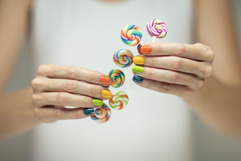 Mooie vrouwenhanden met regenboognagellak die kleurrijke werveling houden lollypops, grappige vrolijk stock afbeelding
