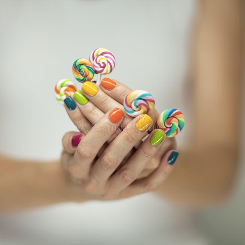 Mooie vrouwenhanden met regenboognagellak die kleurrijke werveling houden lollypops, grappige vrolijk stock foto's