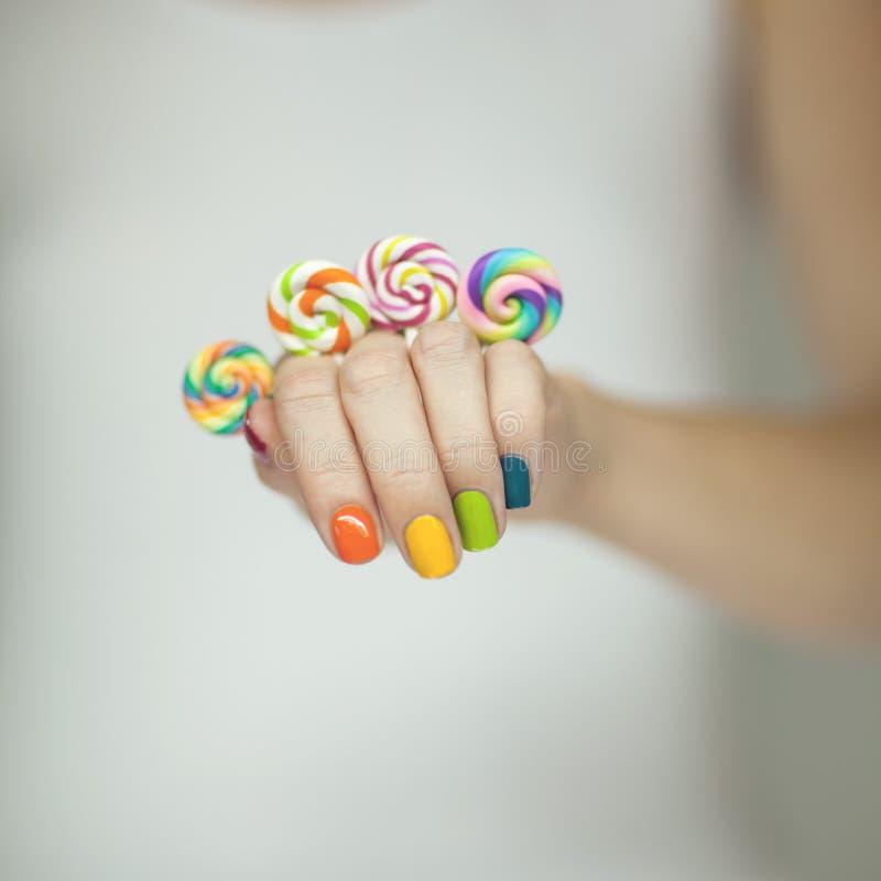 Mooie vrouwenhanden met regenboognagellak die kleurrijke werveling houden lollypops, grappige vrolijk royalty-vrije stock foto