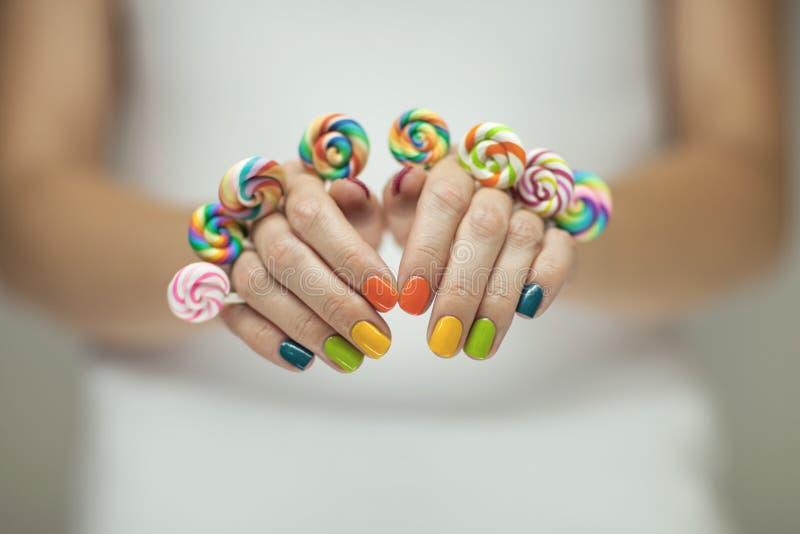 Mooie vrouwenhanden met regenboognagellak die kleurrijke werveling houden lollypops, grappige vrolijk royalty-vrije stock afbeelding