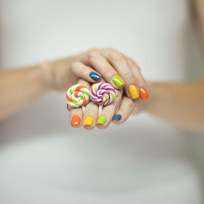 Mooie vrouwenhanden met regenboognagellak die kleurrijke werveling houden lollypops, grappige vrolijk stock afbeeldingen