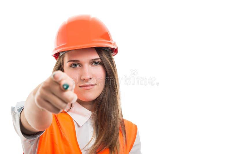 Mooie vrouweningenieur die met veiligheidshelm voorzijde richten stock foto
