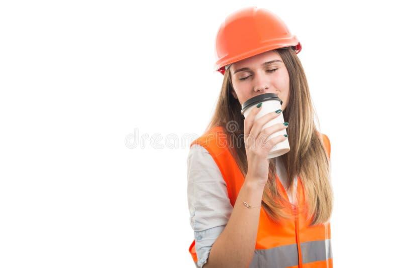 Mooie vrouweningenieur het drinken koffie vóór het werk royalty-vrije stock fotografie