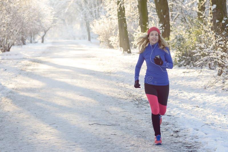 Mooie Vrouwenjogging in de winter met oortelefoons stock afbeelding