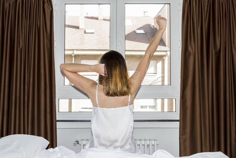 Mooie vrouwenontwaken en het uitrekken zich voor het venster stock afbeelding