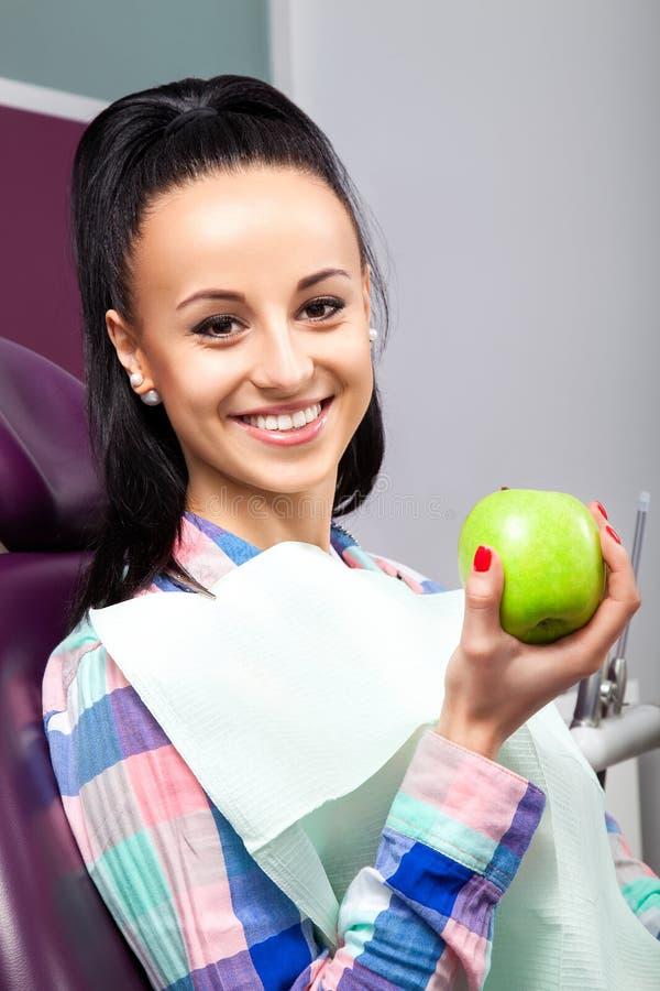 Mooie vrouwenpatiënt die als tandvoorzitter met groene appel glimlachen stock afbeeldingen