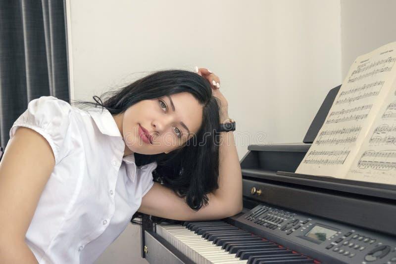 Mooie vrouwenpianist het spelen synthesizer van bladmuziek stock afbeelding