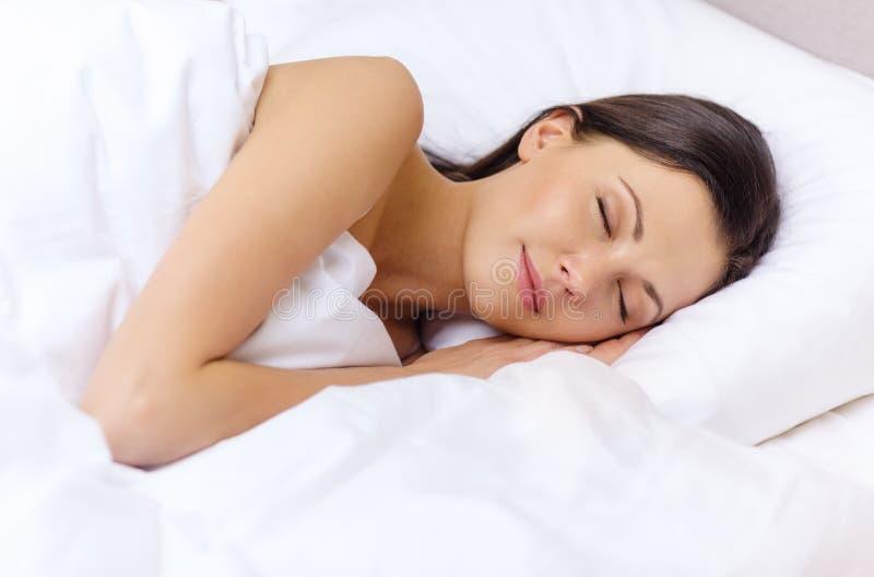 Mooie vrouwenslaap in bed stock foto